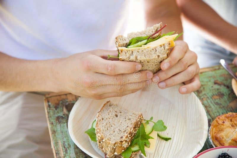 Mani maschii che tengono un panino immagine stock libera da diritti