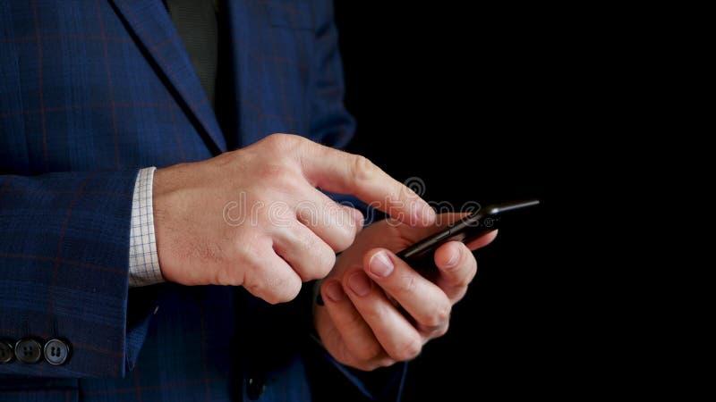 Mani maschii che tengono una fine nera dello smartphone su immagine stock libera da diritti