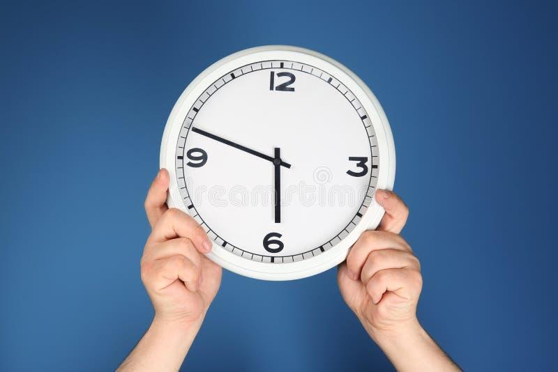 Mani maschii con l'orologio sul fondo di colore Concetto della gestione di tempo immagine stock