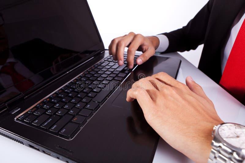 Mani maschii dell'uomo digitante di affari sul computer portatile immagini stock libere da diritti