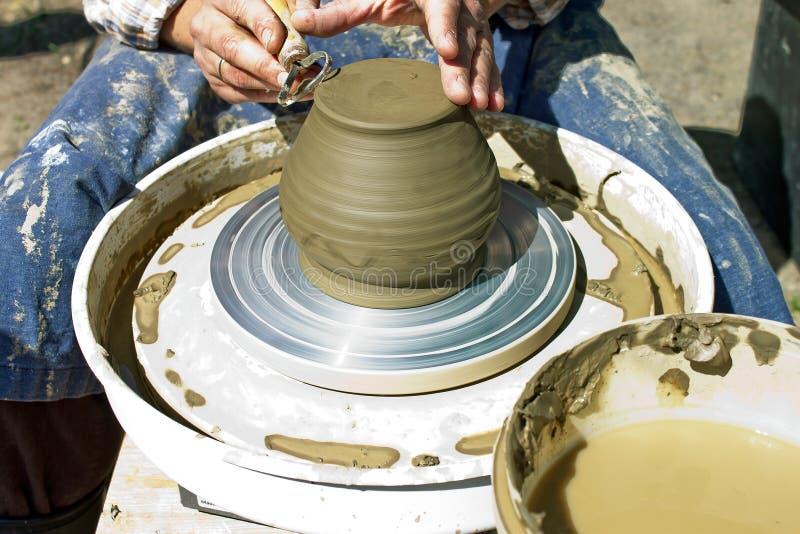 Mani maschii funzionanti su un processo del tornio da vasaio un prodotto dell'argilla sotto forma di brocca fotografia stock libera da diritti