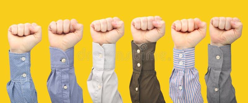 Mani maschii in pugni in camice differenti su fondo giallo fotografie stock