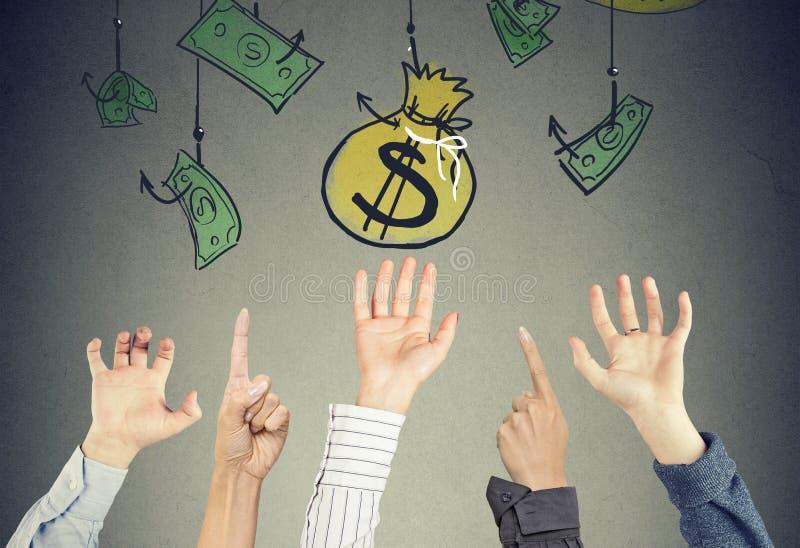 Mani nell'aria che prova a raggiungere la borsa dei soldi che appende sui ganci fotografie stock