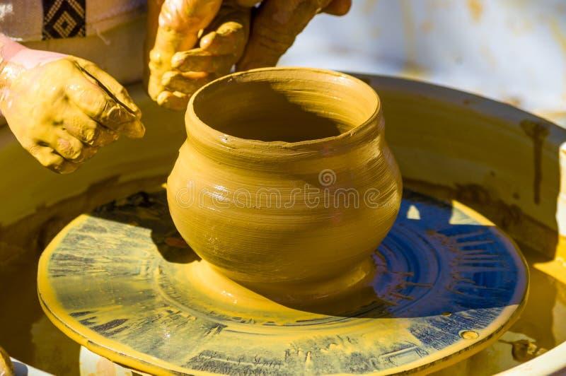 mani nelle delle mani matrici esperte dei bambini e del vasaio, formazione del bambino a produzione di terraglie su un tornio da  immagini stock libere da diritti