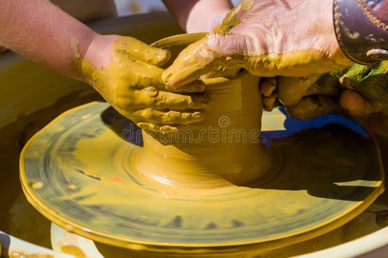 mani nelle delle mani matrici esperte dei bambini e del vasaio, formazione del bambino a produzione di terraglie su un tornio da  fotografia stock