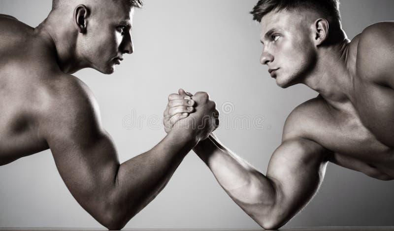 Mani o braccia dell'uomo Mano muscolare Due mani Uomini muscolari che misurano le forze, armi Lottare di braccio dei due uomini r fotografie stock libere da diritti