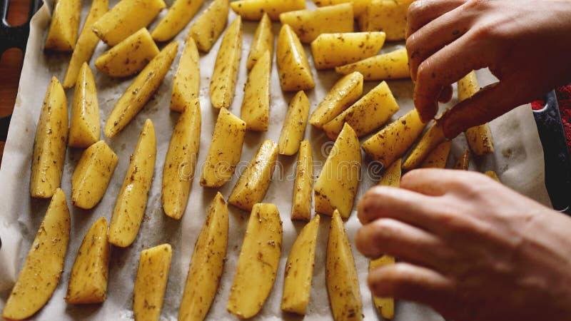 Mani - patate crude affettate su uno strato bollente con le spezie ed i rosmarini, vista superiore fotografia stock