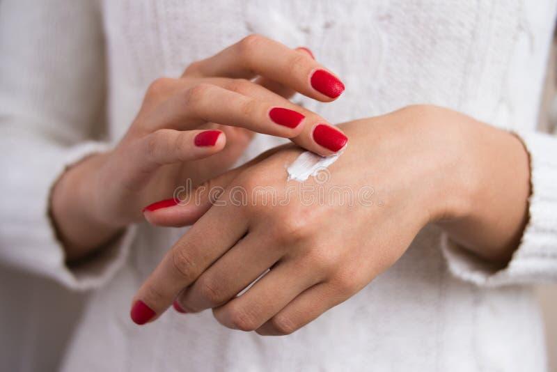 Mani per applicare la crema fotografia stock libera da diritti