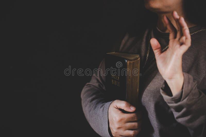 Mani piegate nella preghiera su una bibbia santa nel concetto della chiesa per fede immagine stock libera da diritti