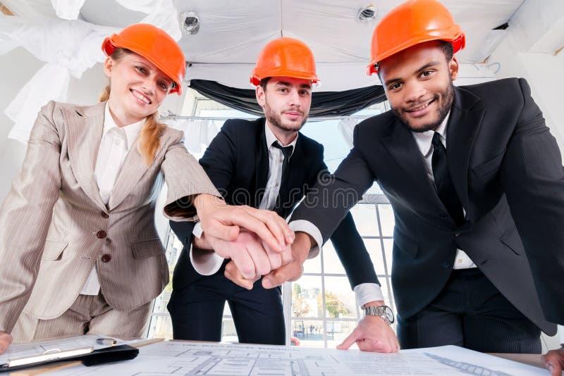 Mani poste architetti sulle mani Un architetto di tre businessmеn incontrato fotografia stock