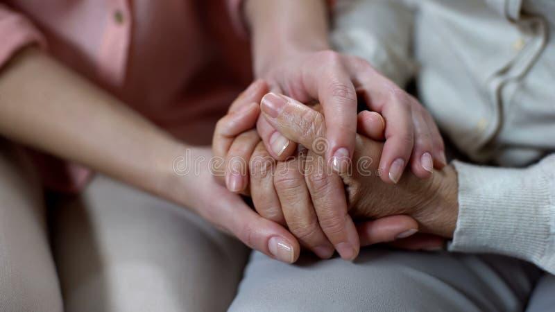 Mani primo piano della madre della tenuta della donna, supporto della casa di cura, amore della famiglia ed aiuto fotografie stock