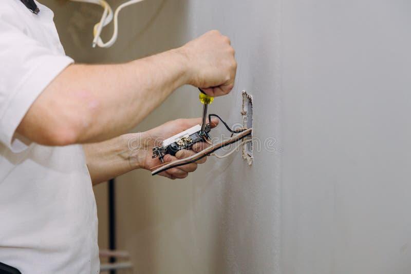 Mani professionali durante il montaggio del connettore elettrico degli sbocchi installato nel muro a secco del pannello di carta  fotografia stock