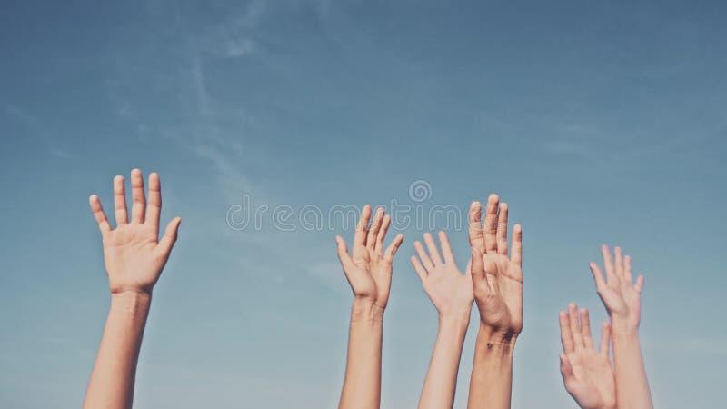 Mani rasing della gente sul fondo del cielo blu Voto, democrazia o concetto di offerta fotografia stock libera da diritti
