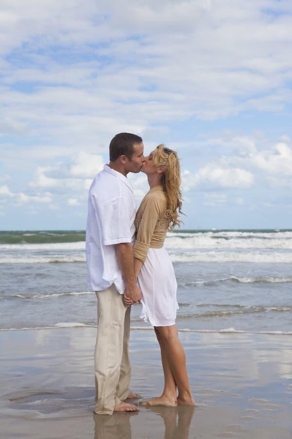 Mani romantiche della holding delle coppie & baciare su una spiaggia immagini stock libere da diritti