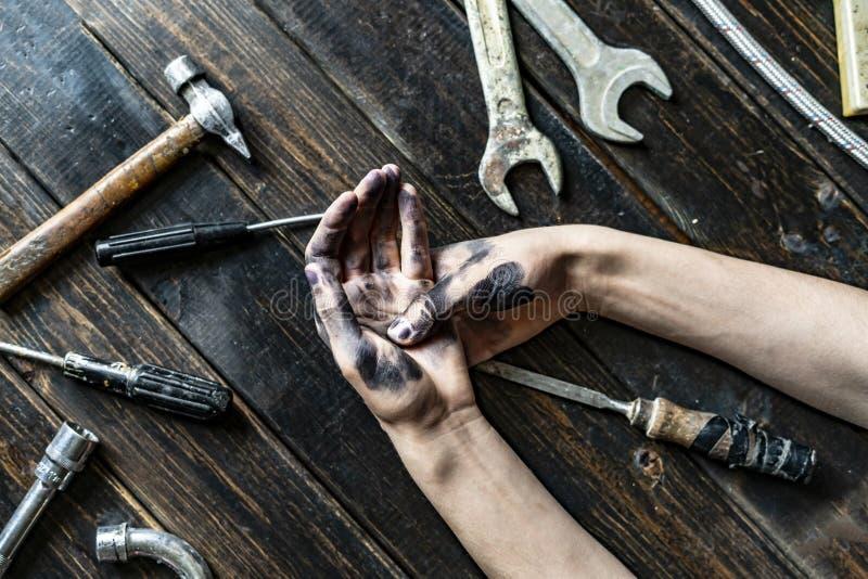 Mani scure sporche della persona della classe del lavoratore sulla tavola di legno con l'attrezzatura f degli strumenti immagini stock libere da diritti