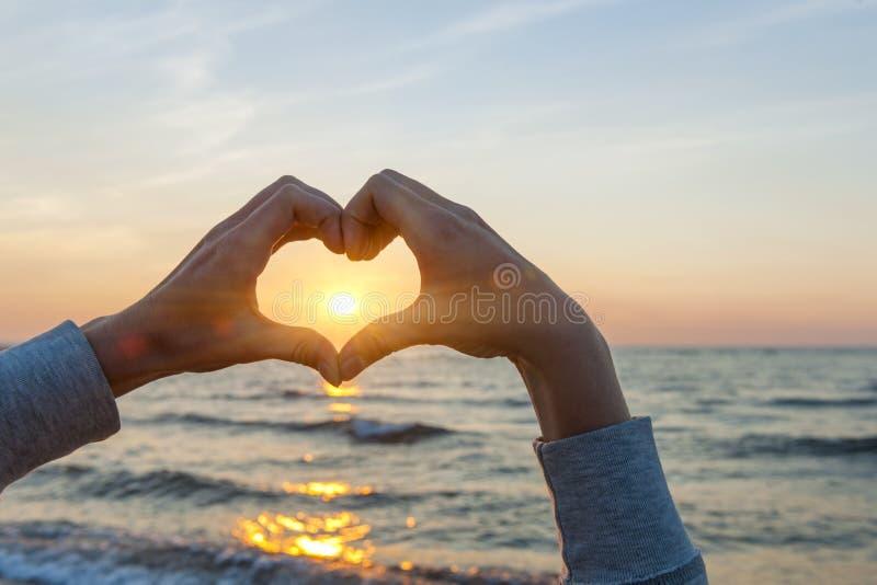 Mani in sole dell'inquadratura di forma del cuore fotografie stock libere da diritti