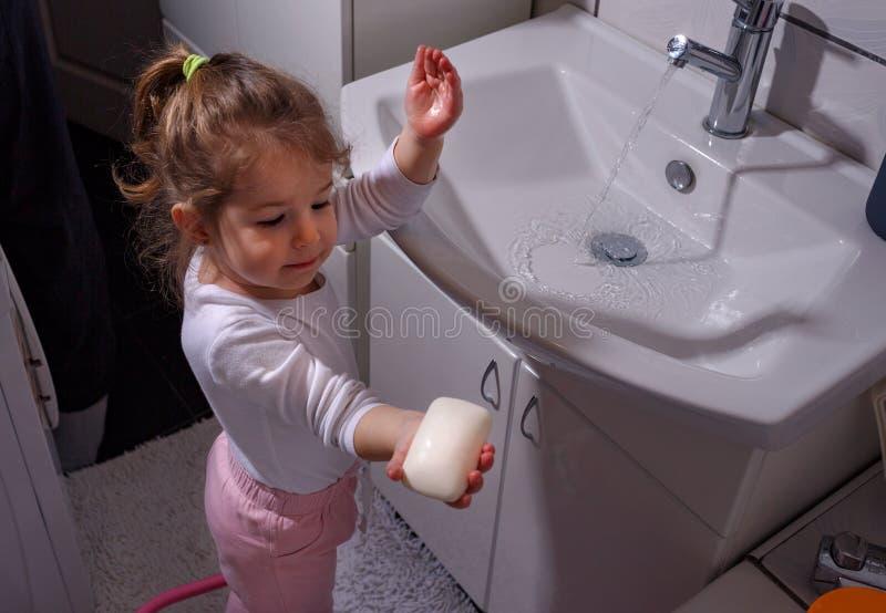 Mani sorridenti di lavaggio della bambina in bagno immagine stock libera da diritti