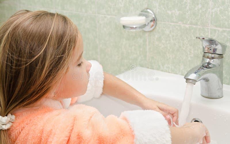 Mani sorridenti di lavaggio della bambina in bagno fotografia stock libera da diritti