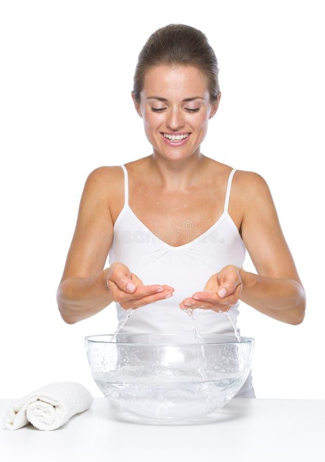 Mani sorridenti di lavaggio della giovane donna in ciotola di vetro con acqua fotografie stock libere da diritti