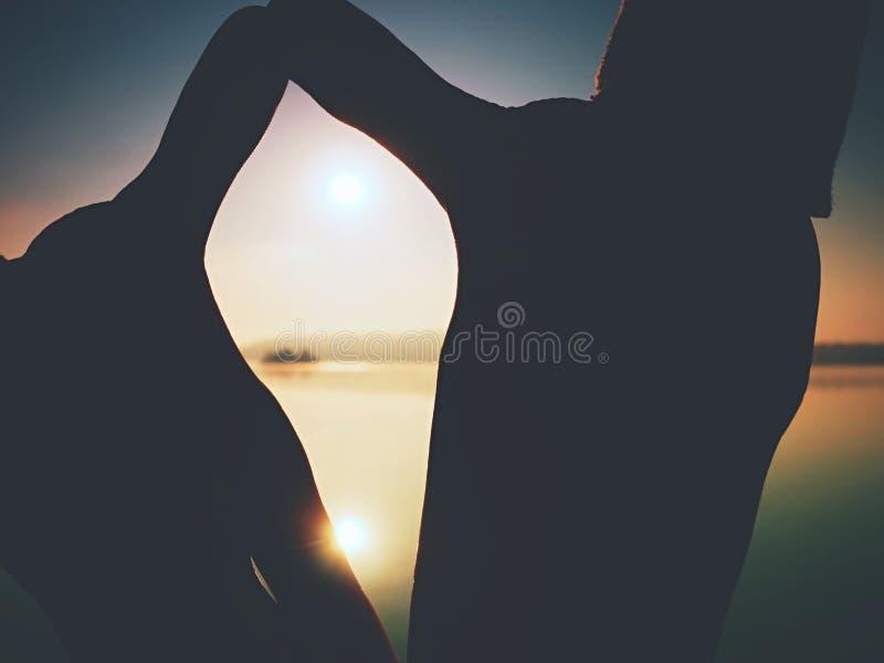 Mani sotto forma della struttura contro il Sun Gioco di ombra sopra il mare fotografie stock libere da diritti