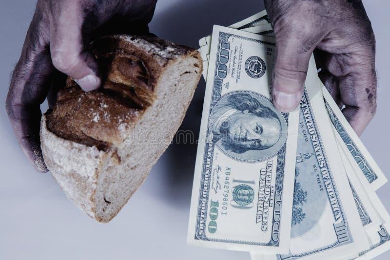 Mani sporche vicine del uo dell'uomo con il pezzo di pane e di soldi come simbolo di povertà, alto costo di alimento immagini stock libere da diritti