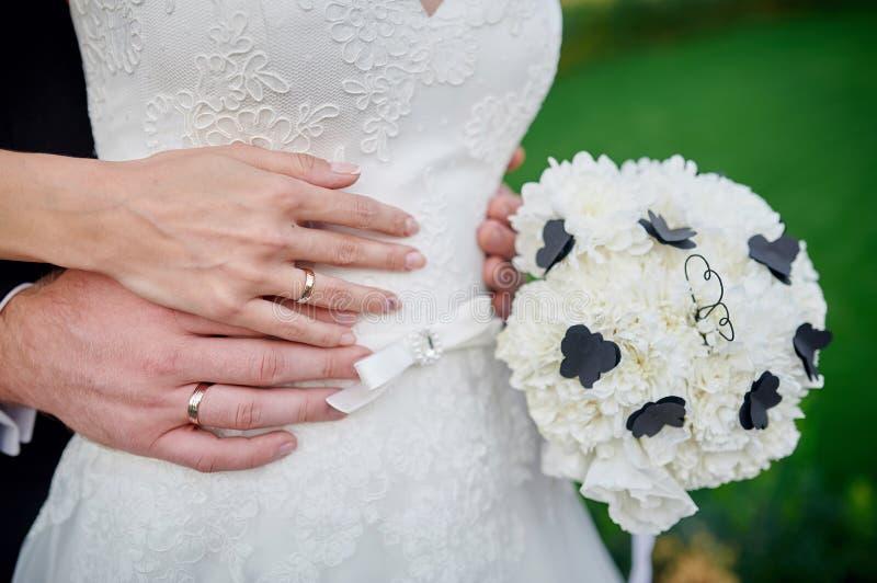 Mani sposa e sposo con le fedi nuziali un mazzo dei fiori bianchi immagine stock libera da diritti
