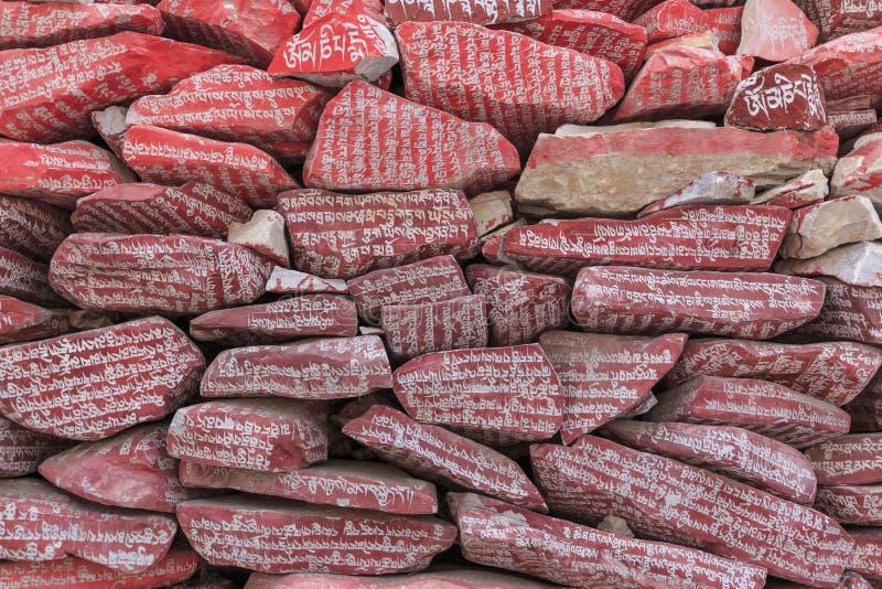 Mani stenar med den buddistiska mantraen Om Mani Padme Hum som inristas i tibetant i Yushu, Kina arkivbilder