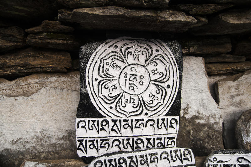 Mani stones. CHAURIKHARKA, NEPAL - CIRCA OCTOBER 2013: Mani stones with the inscription mantra is one of the elements of the Buddhist religion circa October 2013 stock image