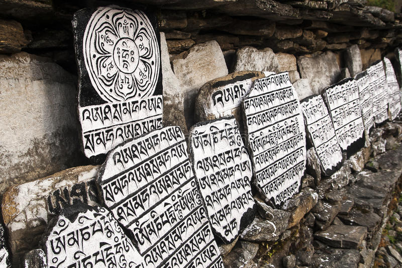 Mani stones. CHAURIKHARKA, NEPAL - CIRCA OCTOBER 2013: Mani stones with the inscription mantra is one of the elements of the Buddhist religion circa October 2013 royalty free stock photo
