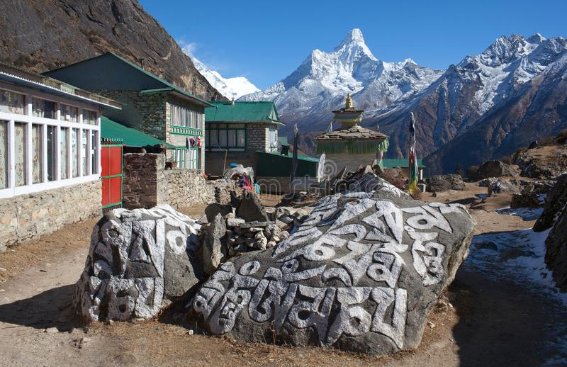 Mani stones in Khumjung village and Ama Dablam mount. Mani stones in Khumjung village and Himalaya mountain landscape on the way to Everest base camp, Khumbu stock photos