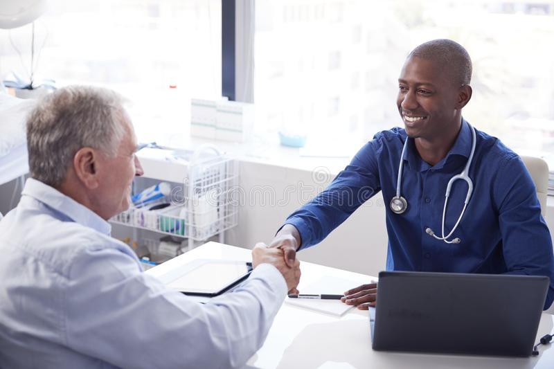 Mani stringere pazienti maschii senior con il dottore Sitting At Desk in ufficio fotografie stock