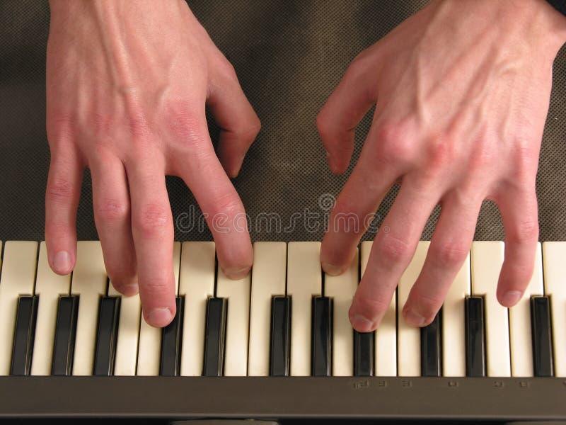 Mani sul piano immagine stock
