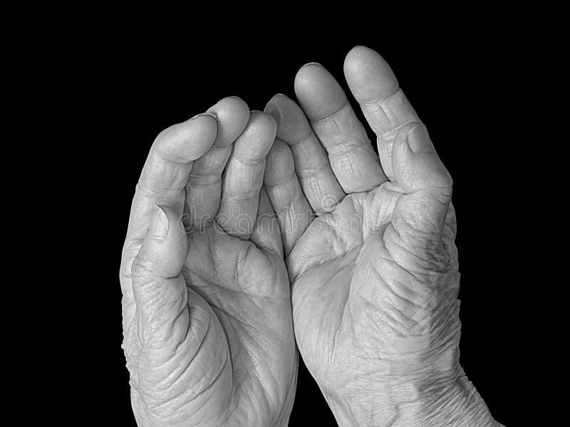Mani tese senior della donna isolate sul nero fotografia stock