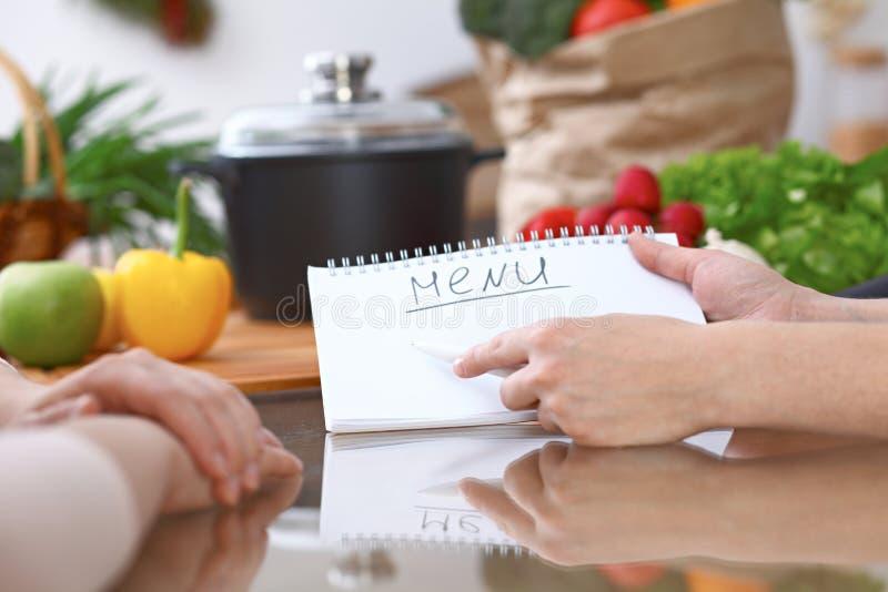 Mani umane che indicano nel taccuino con area di spazio della copia Donna due che fa menu nella cucina, primo piano cottura e fotografia stock
