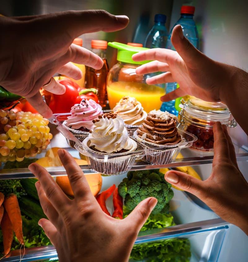 Mani umane che raggiungono per il dolce dolce alla notte nel refrige aperto immagine stock libera da diritti