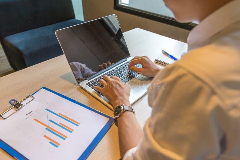 Mani umane che scrivono funzionamento a macchina del computer portatile sul rapporto del grafico di vendite immagine stock libera da diritti