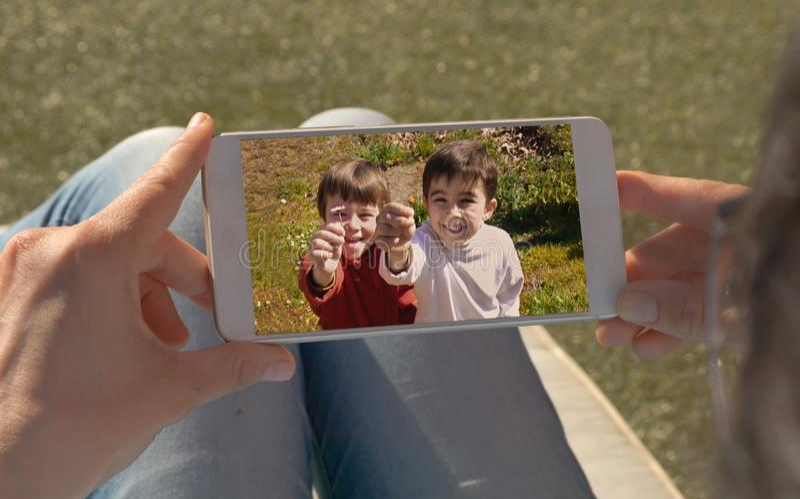 Mani umane che tengono cellulare che esamina un'immagine di due bambini gemellati fotografia stock