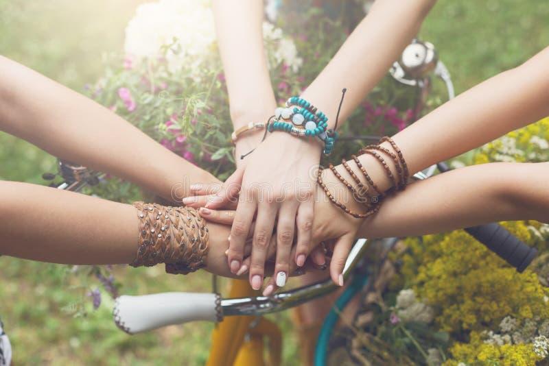 Mani unite delle amiche primo piano, ragazze in braccialetti di boho fotografia stock libera da diritti