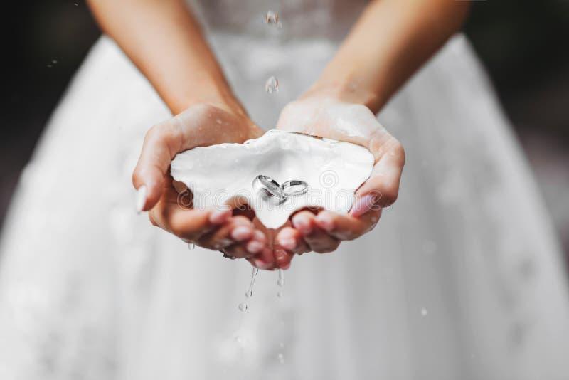 Mani, vestenti una fede nuziale, anelli nella sabbia, anelli sulle coperture immagine stock
