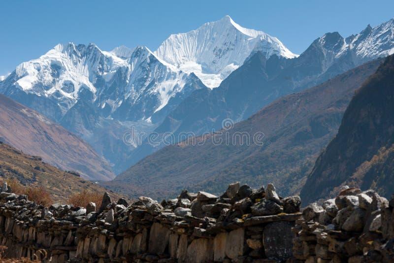 Mani Wall in Langtang Valley, Langtang National Park, Rasuwa Dsitrict, Nepal. Mani Wall in Langtang Valley with Langshisa Peak (Langshisha Ri), Langtang National stock images