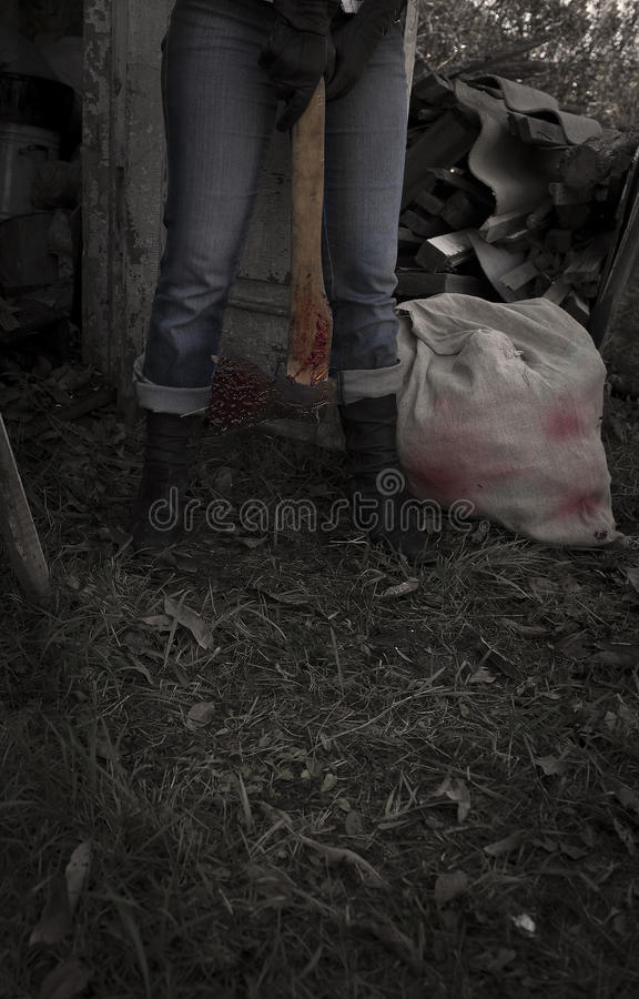 Maniac with bloody axe and sack 2, vertical stock photo