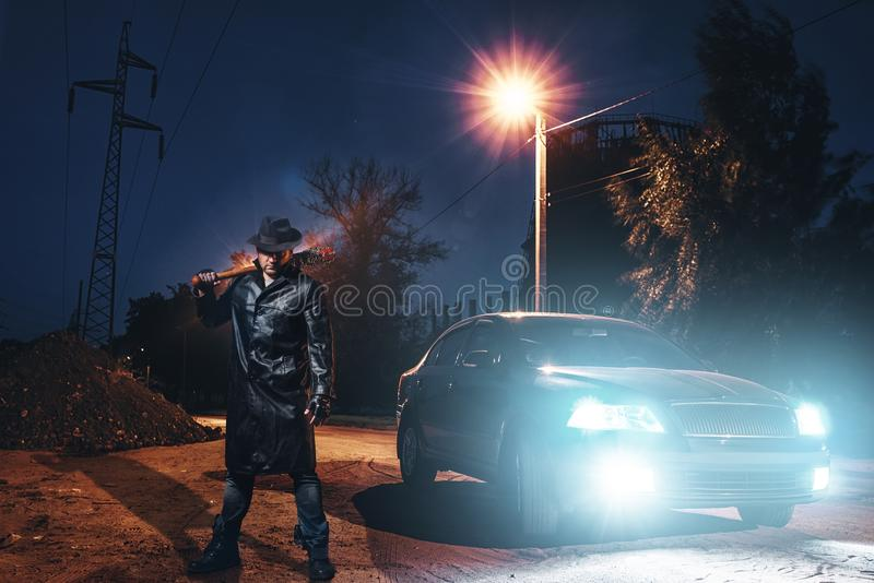 Maniac with bloody baseball bat against black car stock images