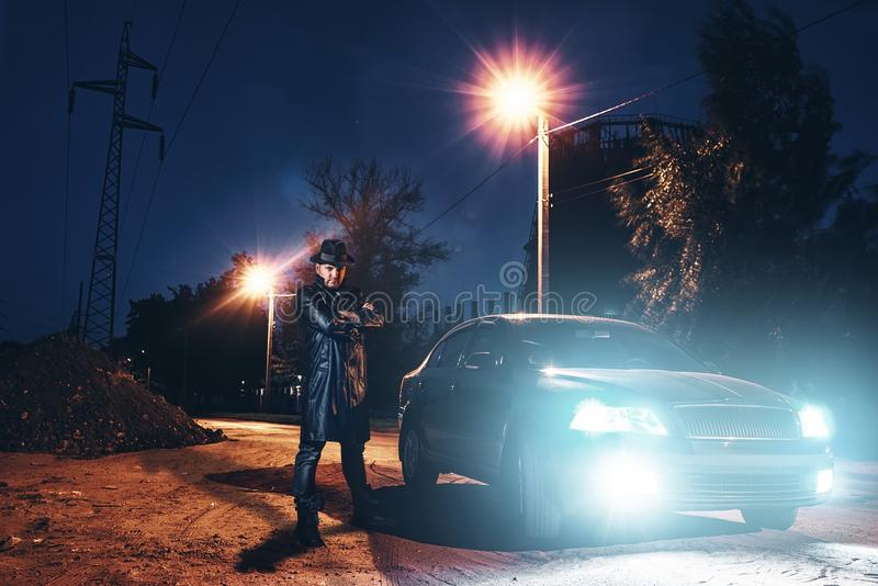 Maniac in leather coat and hat against black car royalty free stock photos