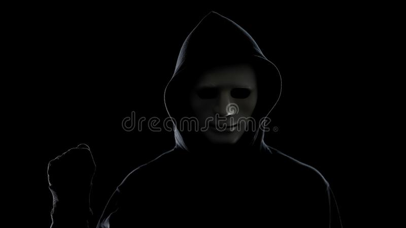 Maniac in white mask and hoodie showing fist, isolated on black background royalty free stock image