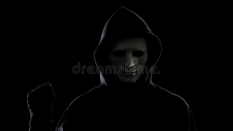 Maniaco en el puño blanco de la demostración de la máscara y de la sudadera con capucha, aislado en fondo negro imagen de archivo libre de regalías