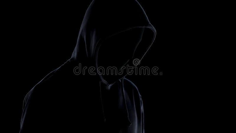 Maniaco peligroso en la situación de la máscara y de la sudadera con capucha contra el fondo negro, crimen imagen de archivo libre de regalías