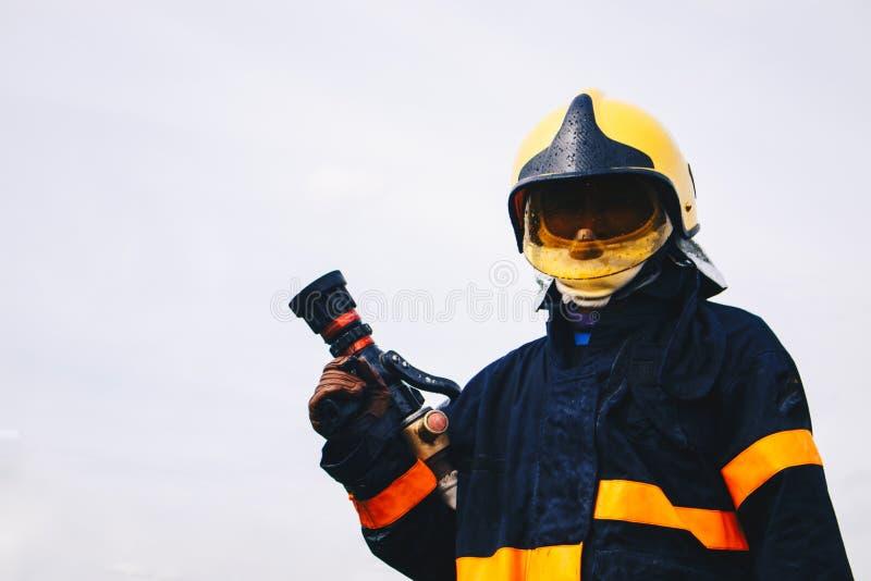 Manichette antincendio della tenuta del pompiere in uniforme ed in una maschera di ossigeno fotografia stock libera da diritti