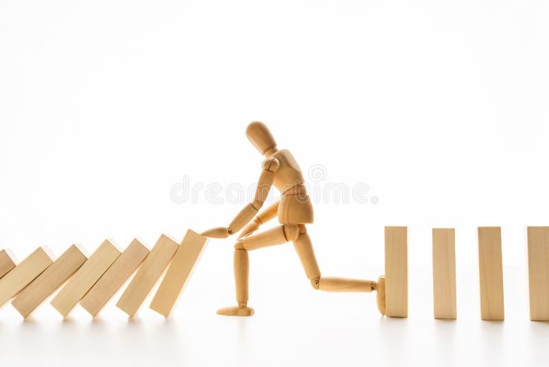 Manichino di legno che ferma effetto di domino su bianco fotografia stock