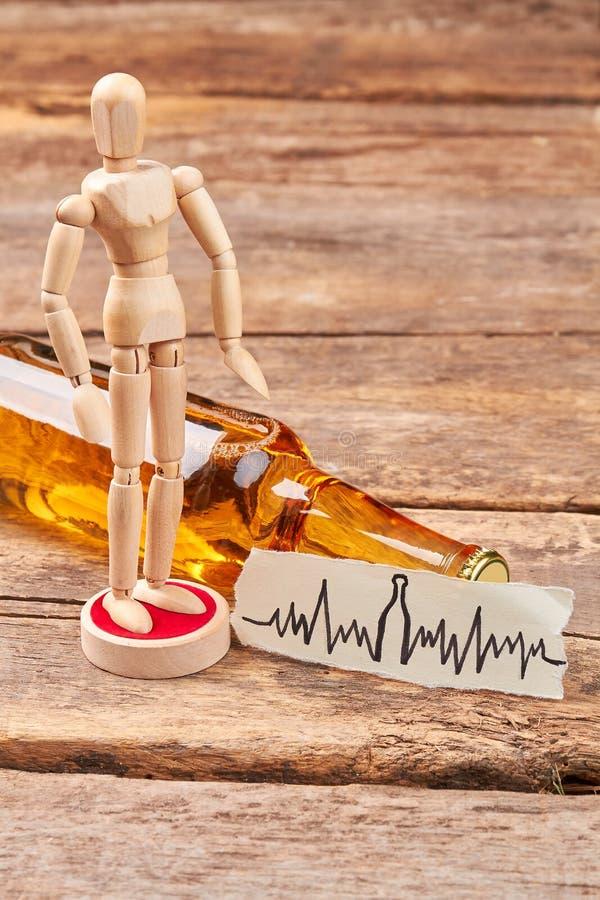 Manichino di legno umano che sta alcool vicino fotografia stock