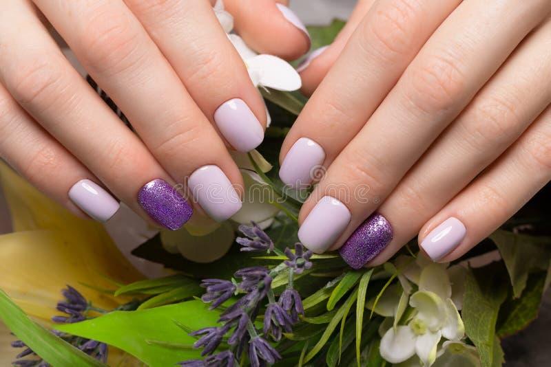 Manicura aseada púrpura en las manos femeninas en fondo de las flores Diseño del clavo fotografía de archivo